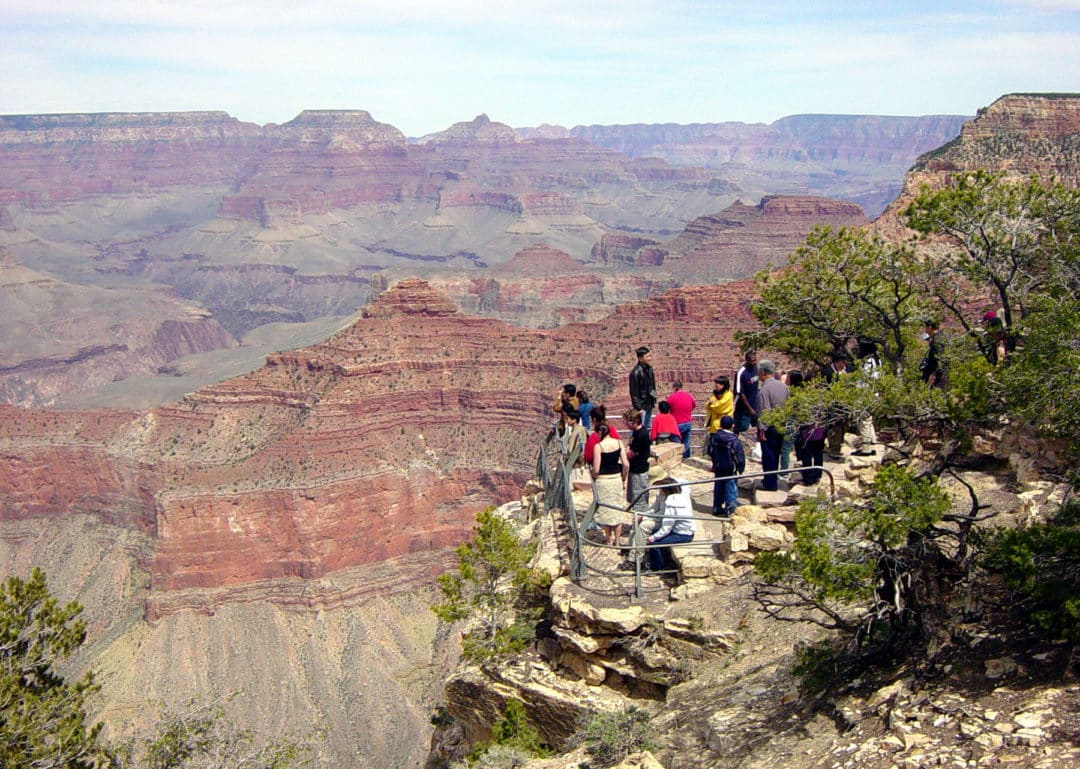VISITORS VIEWING THE CANYON FROM YAVAPAI OBSERVATION STATION ON THE SOUTH RIM OF GRAND CANYON NATIONAL PARK.